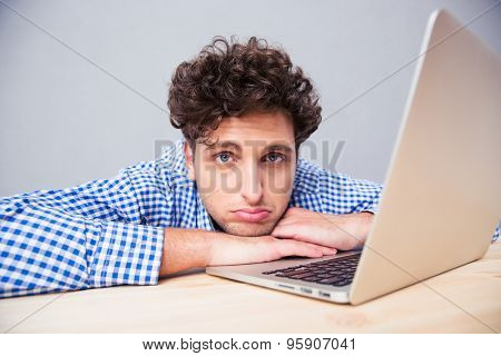 Tired businessman sitting at the table with laptop over gray background and looking at camera