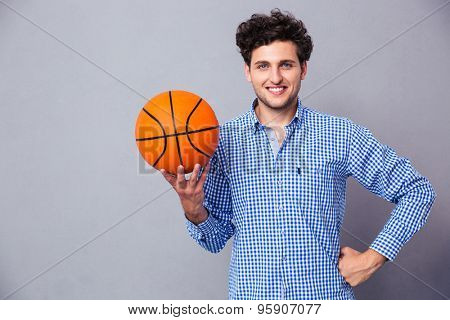Smiling young man holding basket ball over gray background and looking at camera