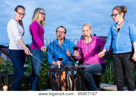 Family at barbecue party in nightly garden with sausages and bread on a stick