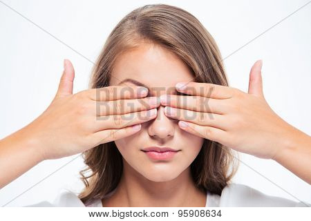 Closeup portrait of a young woman covering her eyes isolated on a white background