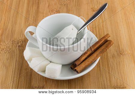 Cup With Tea Bag, Sugar And Cinnamon On Table