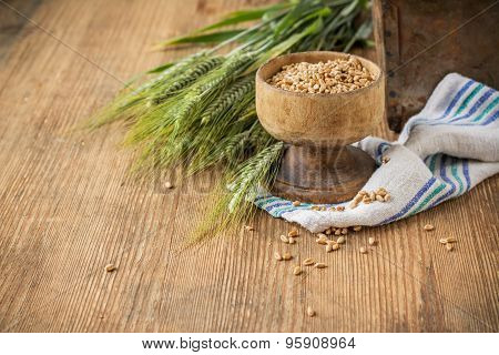 Ears Of Barley And Wheat On The Wooden Background