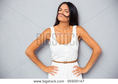 Beautiful woman making mustache with hair over gray background