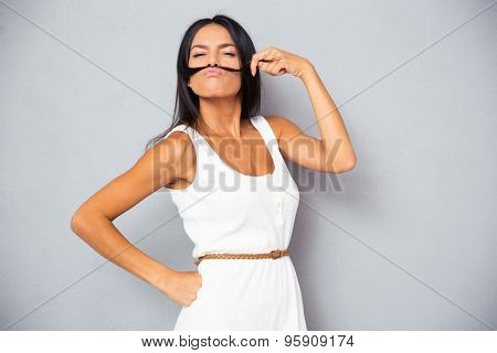 Young woman making mustache with hair over gray background