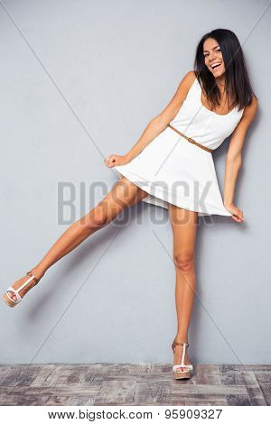 Full length portrait of a funny happy woman standing on one leg over gray background and looking at camera