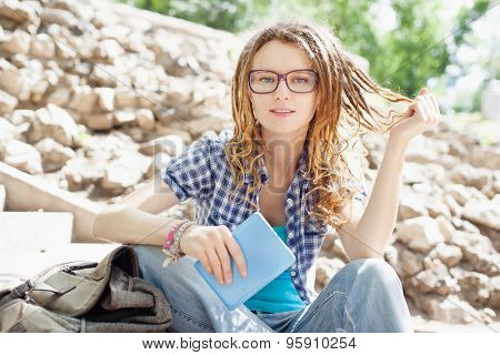 Young cheerful stylish girl with dreadlocks outdoors