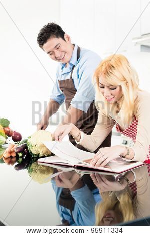 Asian couple reading recipes in cook book
