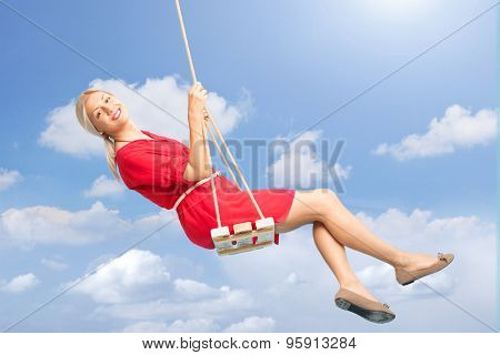 Beautiful blond woman swinging on a wooden swing outdoors on a beautiful summer day