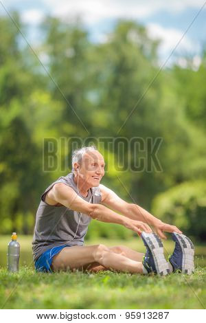 Vertical shot of a senior man stretching his legs seated by a pond in a park and listening to music on headphones