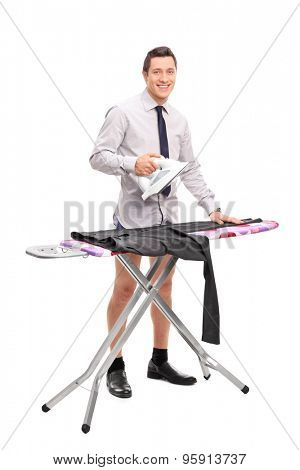 Full length portrait of a young man ironing his pants and looking at the camera isolated on white background