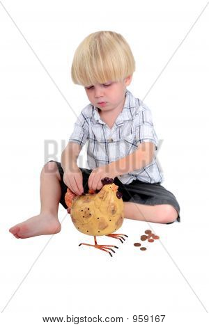 Young Boy Putting Money Into A Piggy Bank