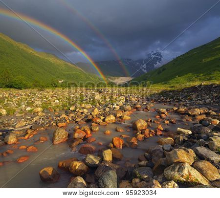 Summer landscape with a rainbow over the mountain river. Beauty in nature