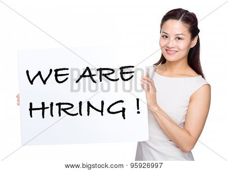 Asian woman holding with placard showing phrase of we are hiring