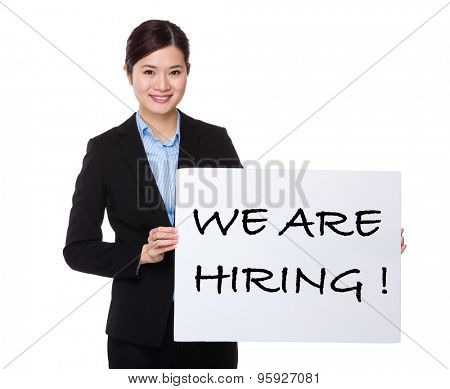 Businesswoman showing a white board with phrase of we are hiring