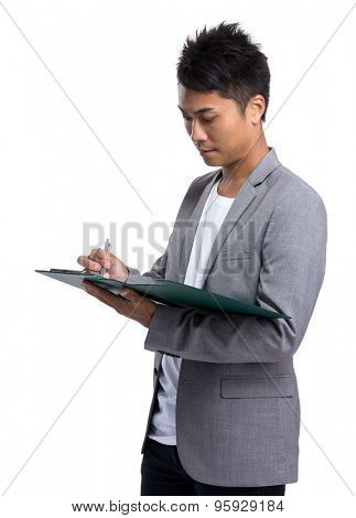 Young businessman write on clipboard