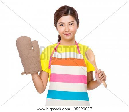Young housewife with cotton gloves and wooden ladle
