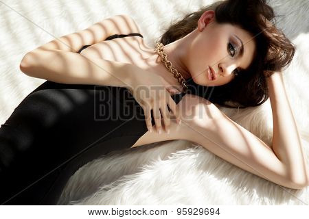 Portrait of a beautiful sensuality and attractive sexy young adult female pretty brunette woman posing in black dress on white fur