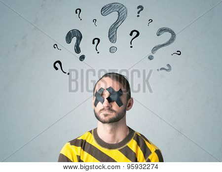 Young man with taped eye question mark symbols around his head