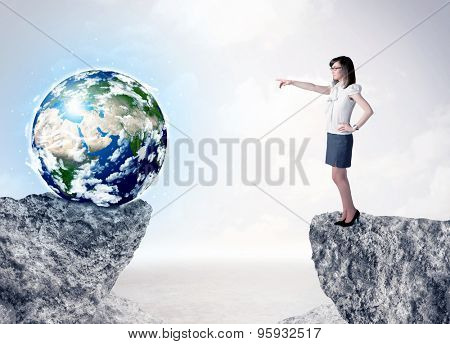 Businesswoman standing on the edge of mountain with a globe on the other side,