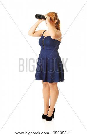 Overweight woman looking through binoculars.