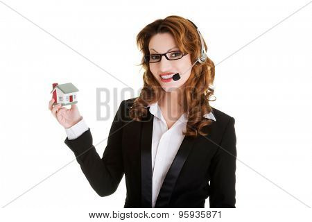 Happy smiling call center woman showing house model.