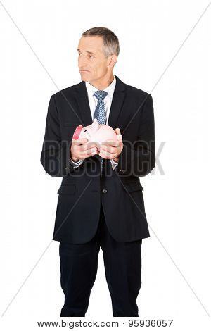 Confused mature businessman holding piggybank.