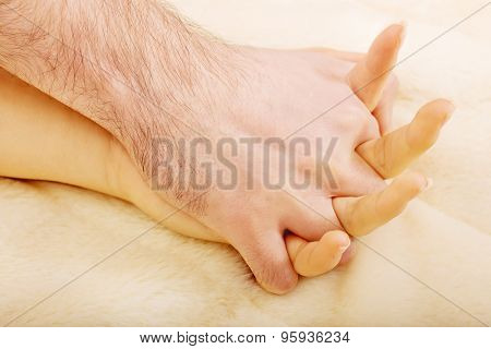 Hands of young couple lying on bed.