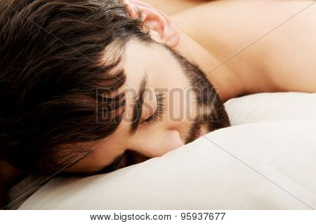 Young exhausted man sleeping in bed.