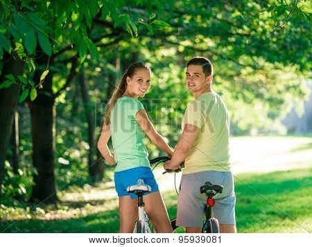 Young couple on bicycles in the park