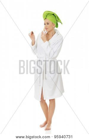 Woman in towel turban smelling parfume.