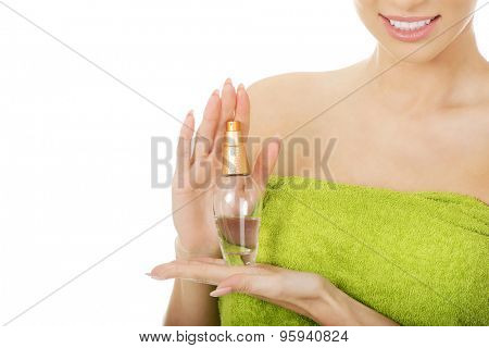 Woman in towel with bottle of parfume.