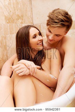 Beautiful young couple enjoying a bath in bathroom.