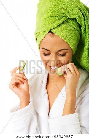 Spa woman in bathrobe eating cucumber.