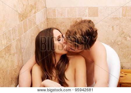 Beautiful young couple kissing a bath in bathroom.