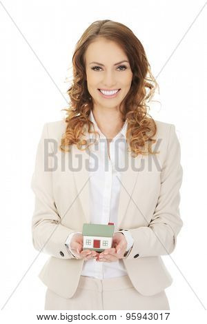 Smiling businesswoman presenting a model house.