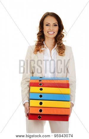 Female office worker carrying heavy binders.