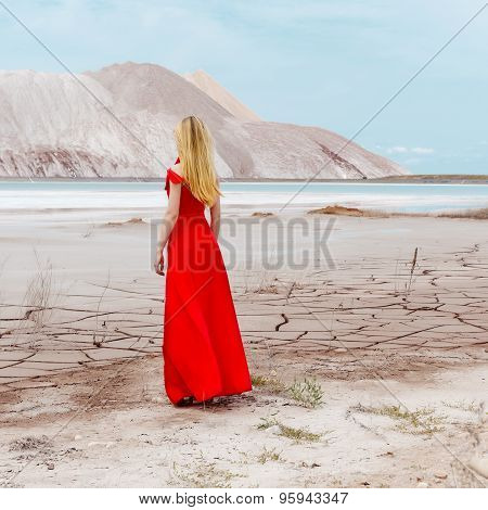 beautiful sexy cute girl with long blond hair in a long red evening dress standing in the desert nea