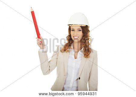 Businesswoman in hard hat pointing up with pencil.