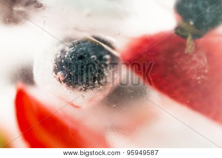 healthy eating, drinks, diet and detox concept - close up of fruit water with strawberry, blackcurrant or blueberry and ice cubes over glass