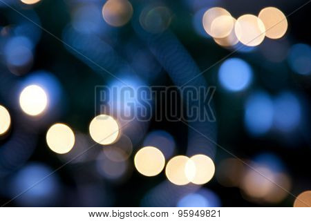 holidays, illumination and electricity concept - colorful bright lights on dark blue night background