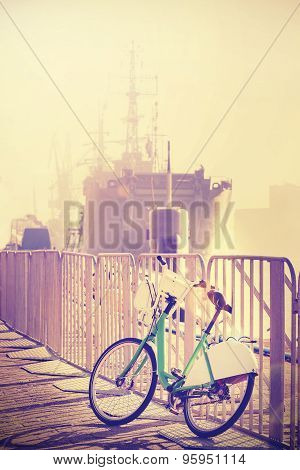 Vintage Toned Bicycle Parked By Pier With Ship In A Distance.