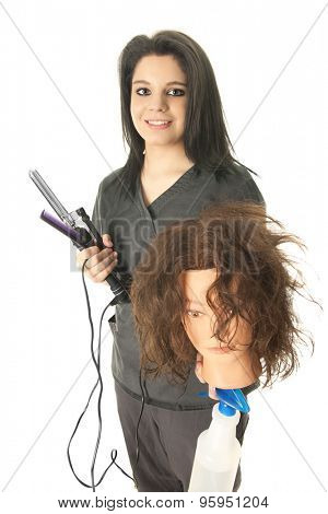 A pretty student cosmetologist happily carrying the equipment she needs to practice hair dressing -- her practice head, a spray bottle of water, comb and curling iron.  On a white background.