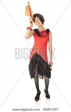 A pretty young teen in a Mexican dance dress happily tipping her straw hat.  On a white background.
