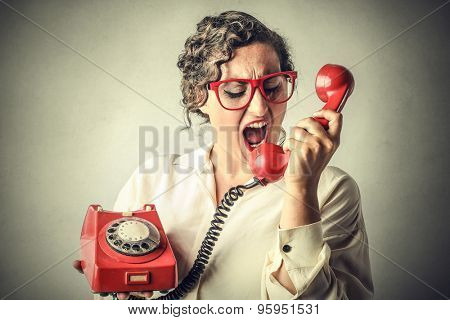 Businesswoman screaming into a red phone