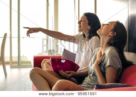Two girls watching tv together