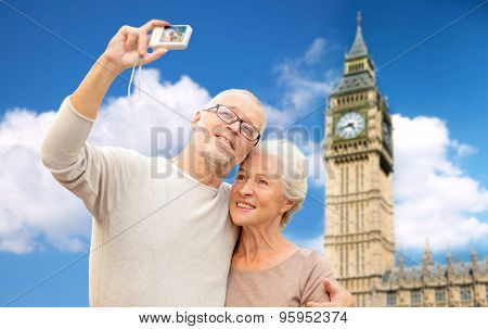 age, tourism, travel, technology and people concept - senior couple with camera taking selfie over big ben tower in london city background