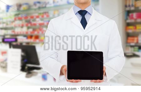 medicine, technology, advertisement, pharmacy and healthcare concept - smiling male doctor with tablet pc computer over drugstore background