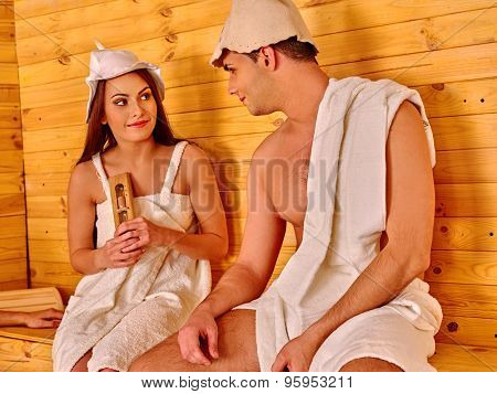 Couple young  people in hat  relaxing at sauna.