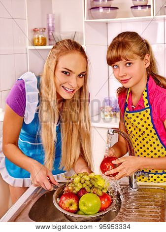 Happy family with girl kid  washing fruit at kitchen.