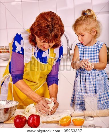 Grandmother and granddaughter baking cookies. Two people.